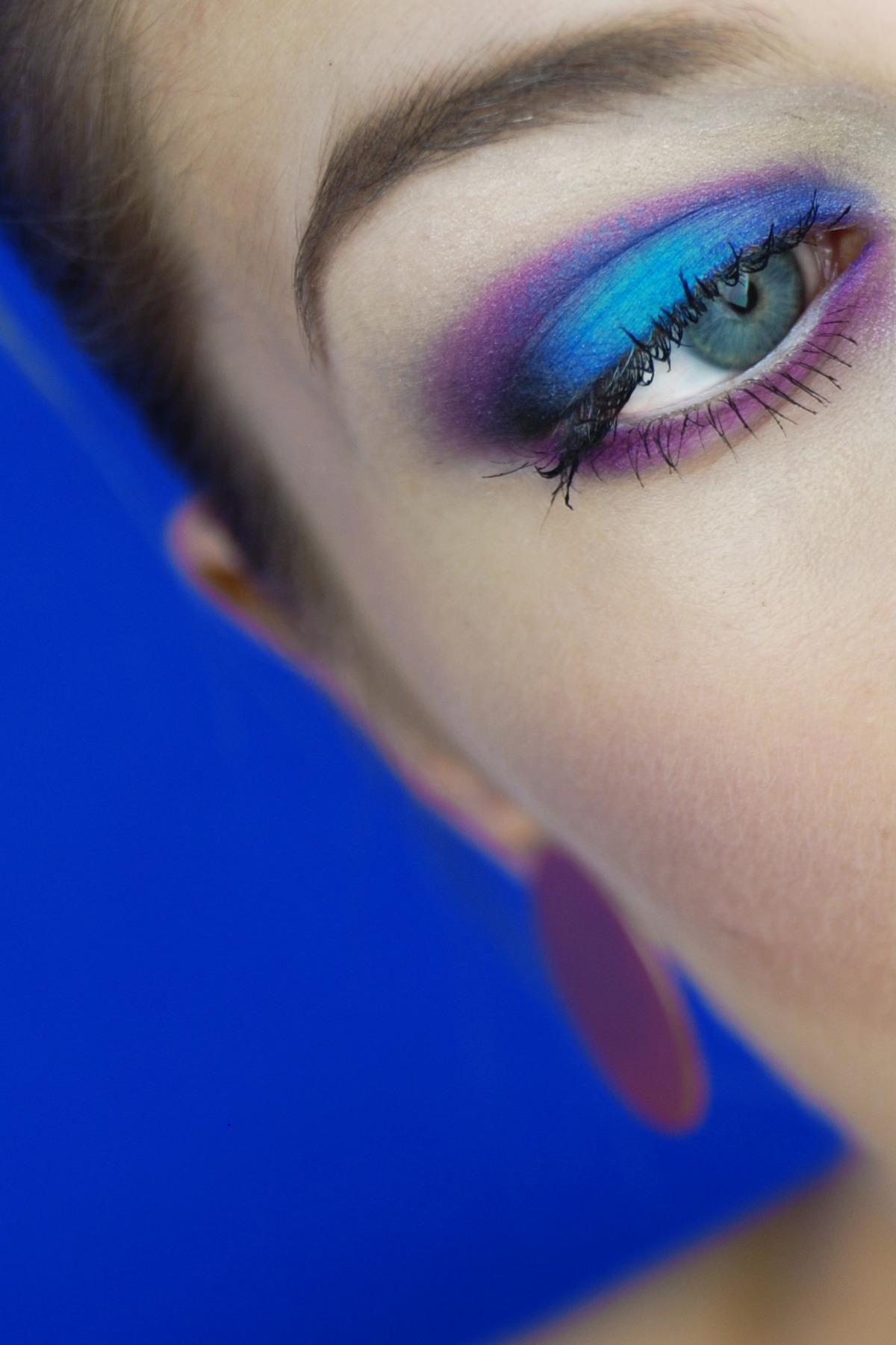 Zdjęcie przedstawia zbliżenie na oko kobiety pomalowane na niebiesko-fioletowo, całość na niebieskim tle.